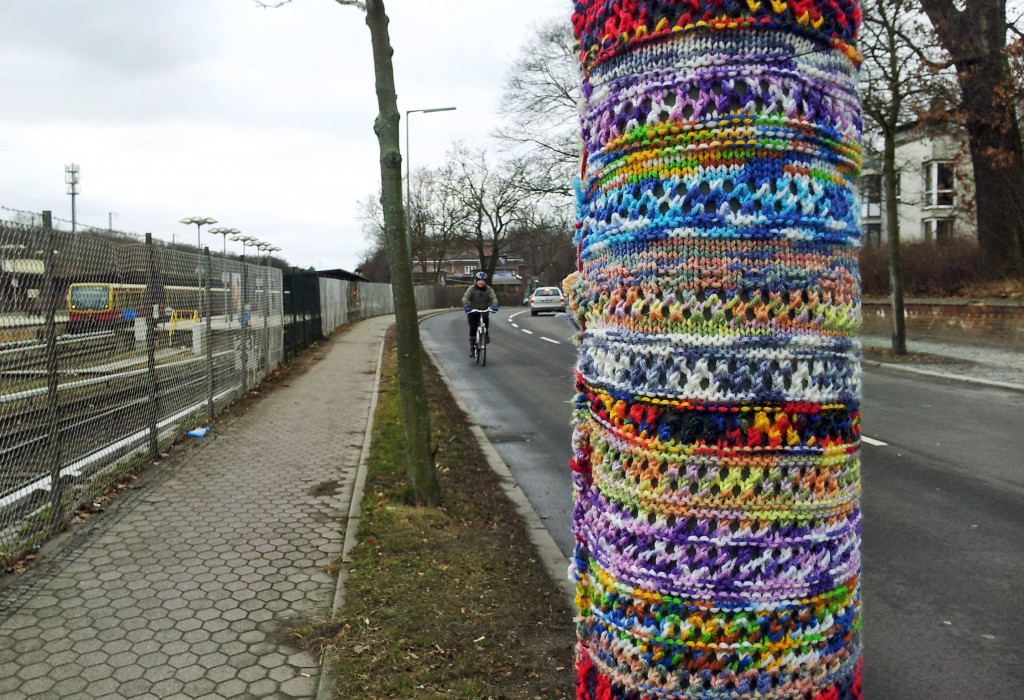 an example of guerilla knitting in the city in berlin Germany, a lamp post covered with colorful knitting