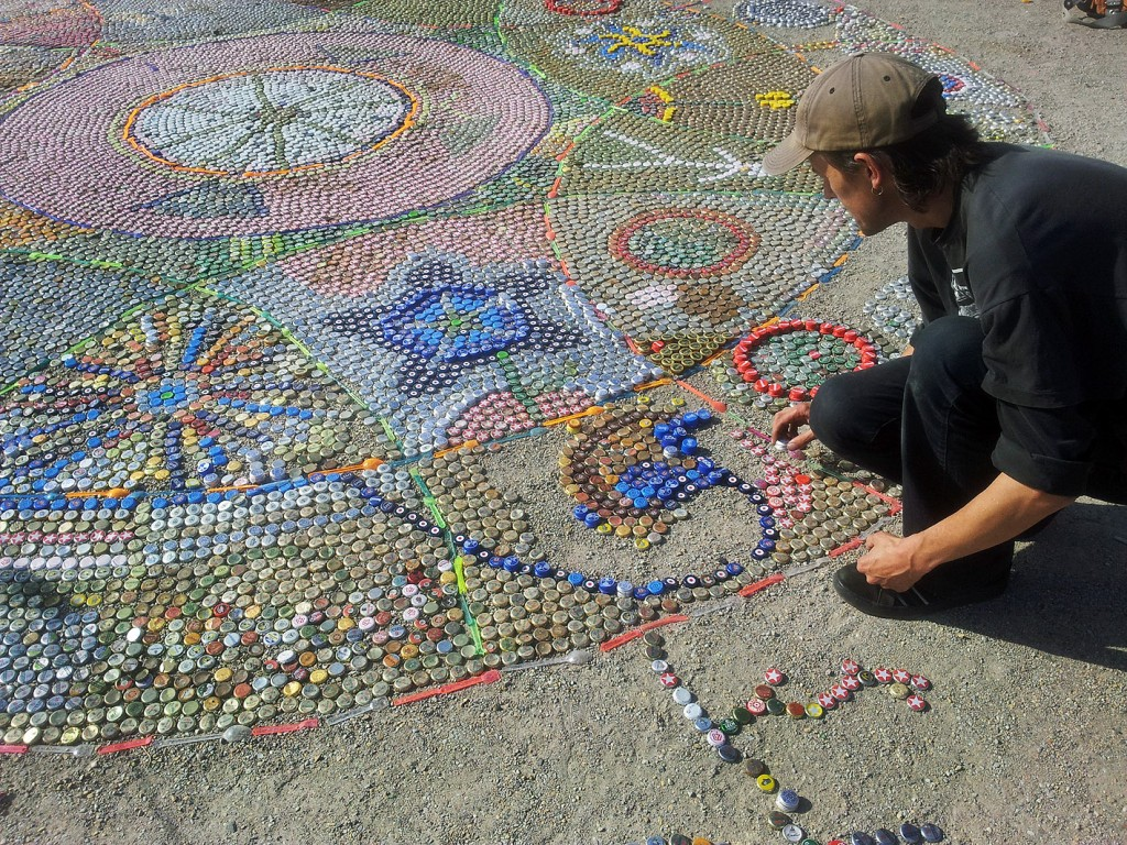 Portrait of artist Mathias Waller placing bottle caps into his ground mosaic in Görlitzer Park, Berlin Germany