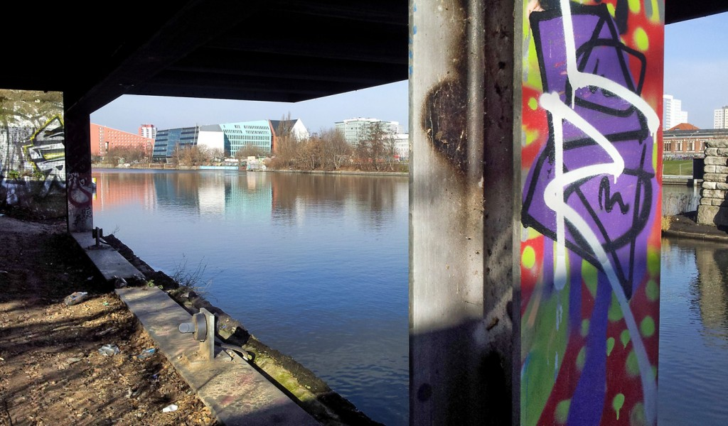 View of the sunny Spree from graffiti sprayed bridge