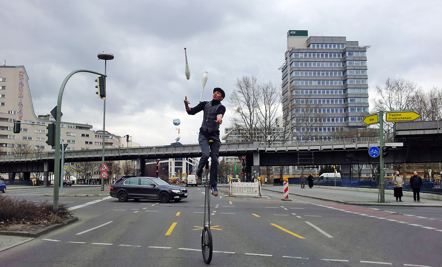 photo of a young man in Berlin who is juggling three pins while sitting on a unicycle