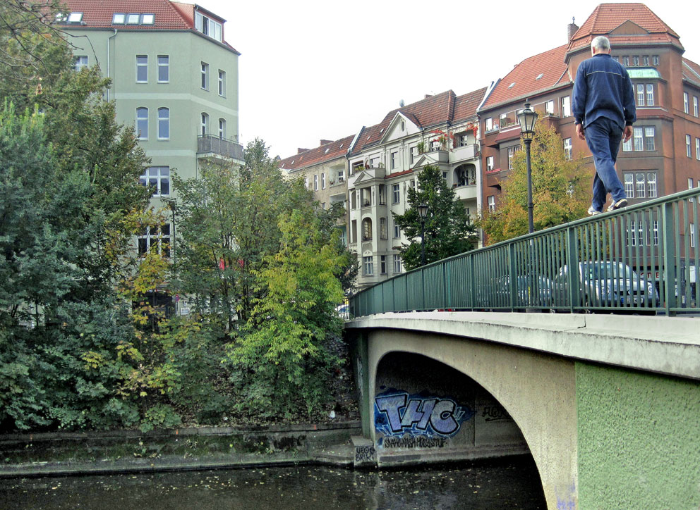 Man walking on the railing of a bridge in Berlin-Kreuzberg