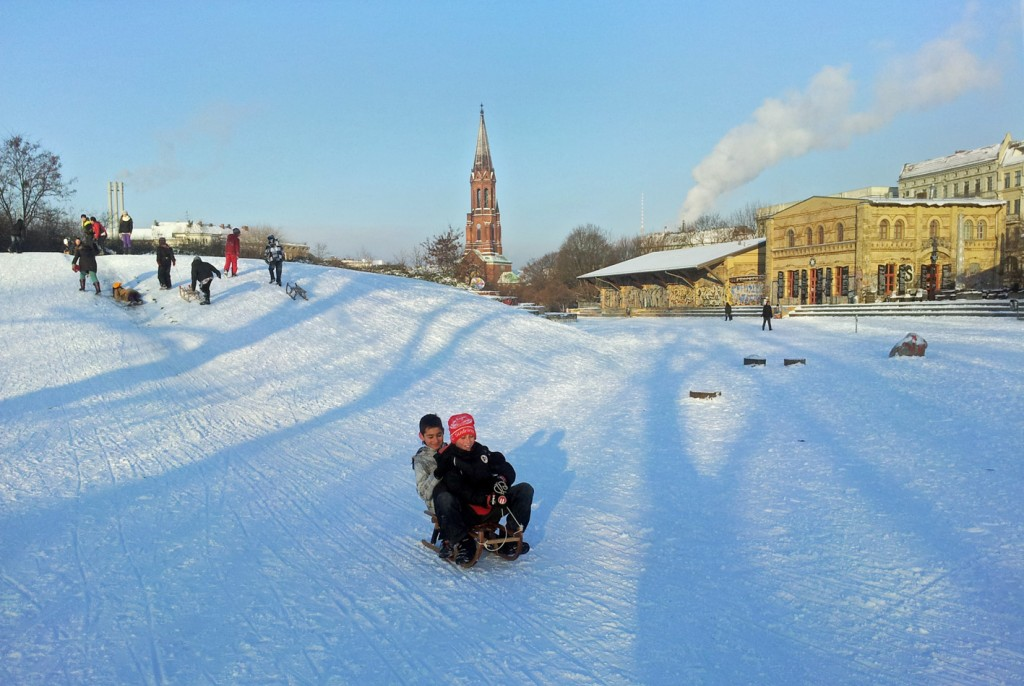 Two kids on a sled, riding down a hillin Görlitzer Park, in Berlin- Kreuzberg